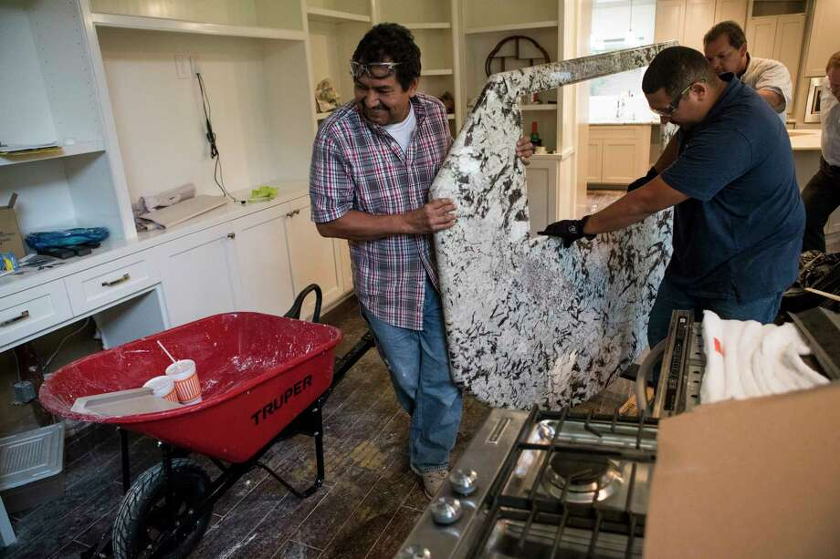 Oscar Cerritos, left, and Louis Cerritos carry out a granite countertop during restoration work of a Meyerland area home, that was flooded in the aftermath of Hurricane Harvey. The house had been newly renovated and is now being gutted by Legal Eagle Contractors. Photo: Brett Coomer, Staff / © 2017 Houston Chronicle