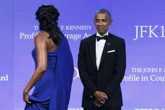 Former U.S. President Barack Obama watches as his wife, Michelle Obama, exits the stage after he received the John F. Kennedy Profile in Courage Award at the the John F. Kennedy Presidential Library and Museum in Boston on May 7, 2017.