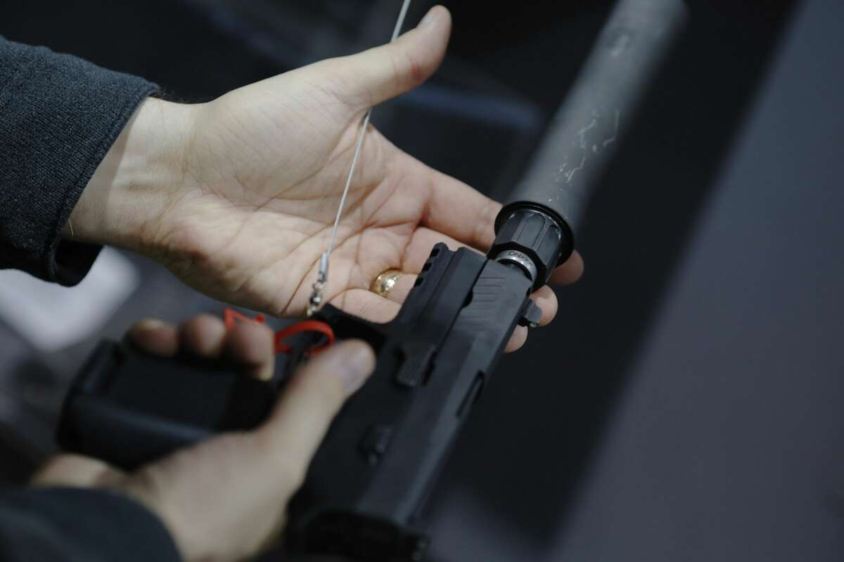 A visitor holds a pistol with a silencer at a gun display during a National Rifle Association outdoor sports trade show on February 10, 2017 in Harrisburg, Pennsylvania. The Great American Outdoor Show, a nine day event celebrating hunting, fishing and outdoor traditions, features over 1,000 exhibitors ranging from shooting manufacturers to outfitters to fishing boats and RVs, and archery to art.