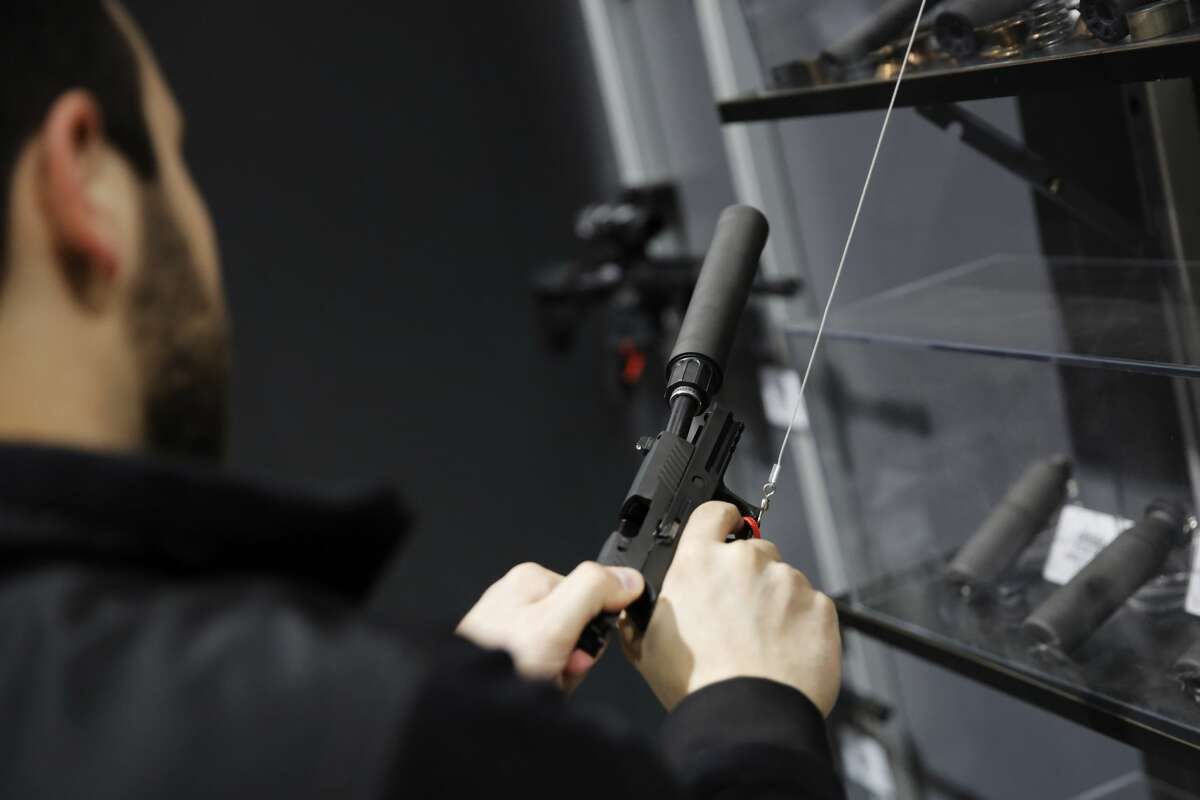 A visitors pulls the slide of a pistol with a silencer at a gun displays at a National Rifle Association outdoor sports trade show on February 10, 2017 in Harrisburg, Pennsylvania.