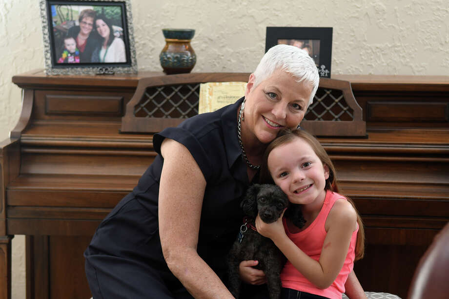"""Karen Sharpe with her granddaughter Kylie, 6½, and 7-year-old Toy Poodle """"Toby,"""" enjoy an afternoon at home in Cypress. Photo: Jerry Baker, Freelance / Freelance"""