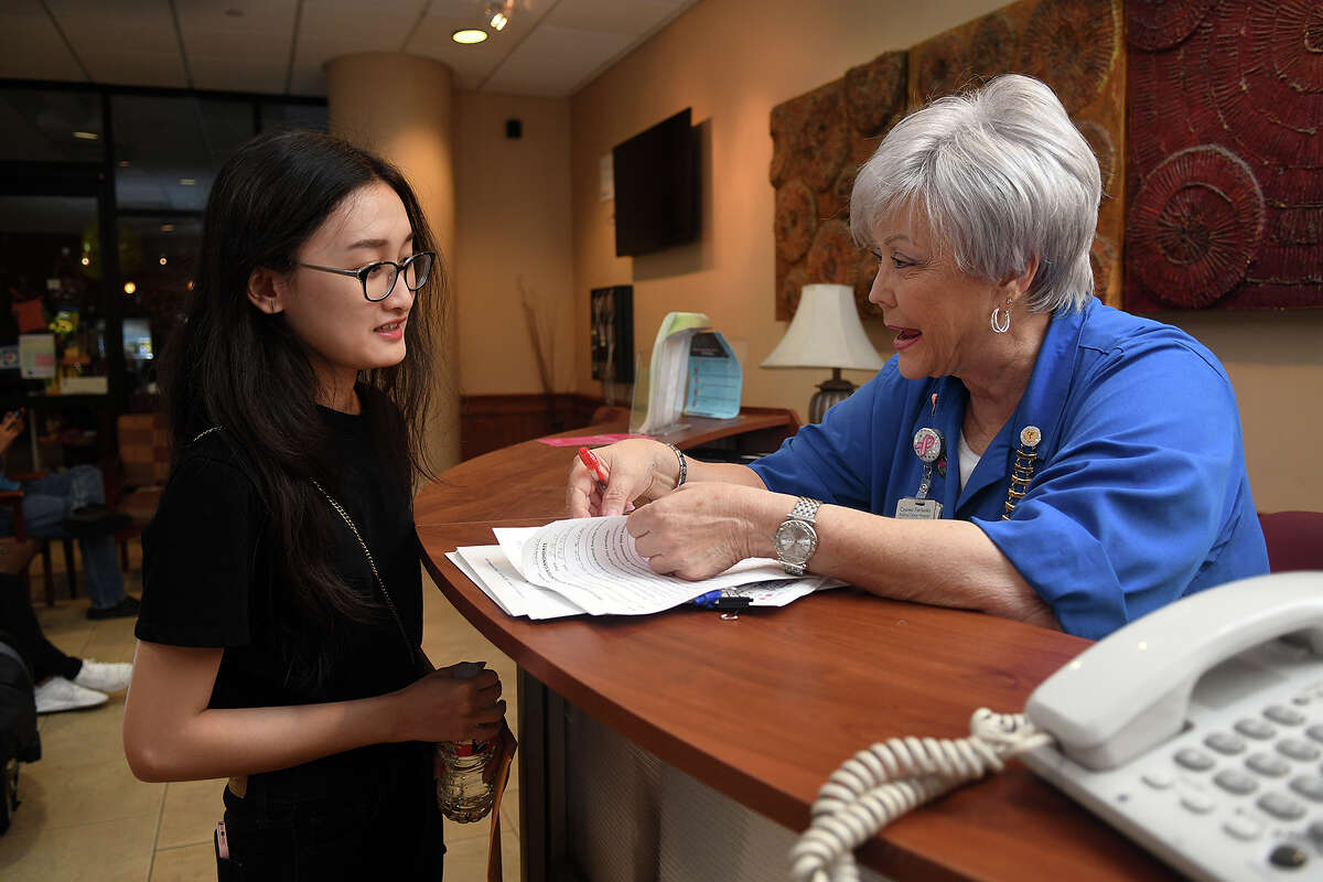 Georgi Landau, right, a breast cancer survivor and volunteer at Cypress Fairbanks Medical Center, interviews prospective volunteer Khanh Nguyen, 20, of Cypress, a pharmacy student at Lone Star College -Tomball, at the information desk at the medical center.