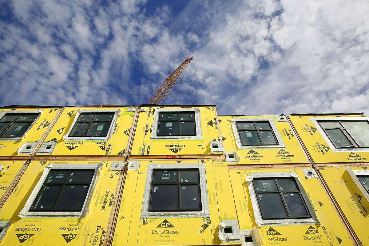 A 136-unit rental housing project takes place in the Bayview in San Francisco, Calif., on Monday, September 28, 2015. On it's sixth day, the modular housing units are a little more than a third of the way stacked as they work on four floors.