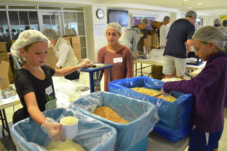 Darien girls, from left, Ainsley McKee, 11, Jessica Schmidt, 12, and Kate Edwards, 11, pitch in at the 9th annual Feed My Starving Children food packing event at Middlesex Middle School, Saturday, Sept. 30, 2017, in Darien, Conn. Photo: Jarret Liotta / For Hearst Connecticut Media / Darien News Freelance
