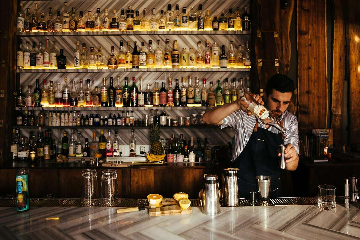 Alex Alotte pours the apricot liqueur into the glass at Biig in San Francisco, Calif. Monday, October 2, 2017.