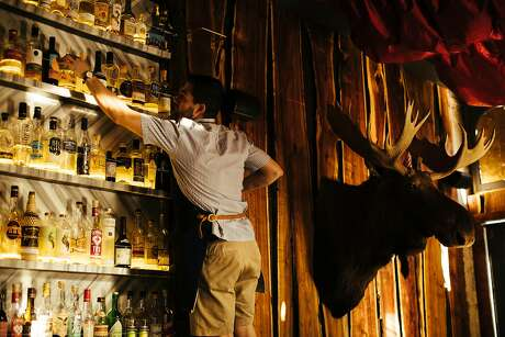 Alex Alotte reaches for a bottle of Moletto gin at Biig in S.F. Photo: Mason Trinca, Special To The Chronicle