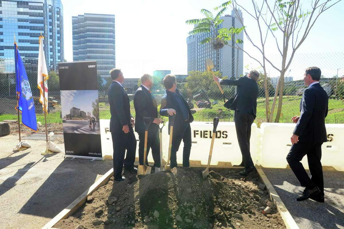 Stamford mayor David Martin, second from right, flings dirt into the pit during the groundbreaking ceremony for Parcel 38, also known as the hole downtown, in Stamford, Conn. on Tuesday, Oct. 3, 2017. Also pictured, from left, Director of Development at F.D. Rich Chris Kelly, Stamford Director of Public Safety, Health and Welfare Ted Jankowski, President of Ironstate Development Co. David Barry and Stamford Director of Administration Michael Handler.