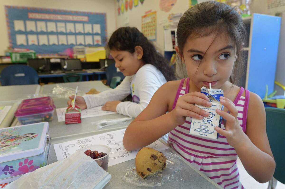 First-graders Emily McGuire and Ashley Delcid take part in Brookside Elementary School's breakfast program Tuesday, Sept. 26, at the school in Norwalk. Norwalk Public Schools has been awarded a $52,000 grant from the American Association of School Administrators to expand its