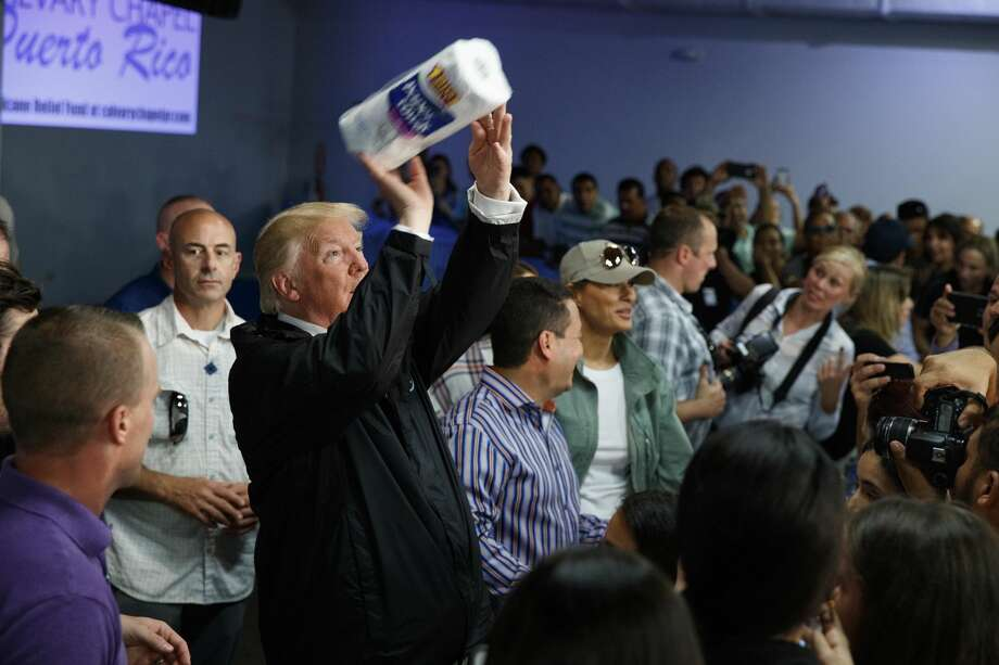 President Donald Trump tosses paper towels into a crowd as he hands out supplies at Calvary Chapel, Tuesday, Oct. 3, 2017, in Guaynabo, Puerto Rico. Trump is in Puerto Rico to survey hurricane damage. (AP Photo/Evan Vucci) Photo: Evan Vucci/AP