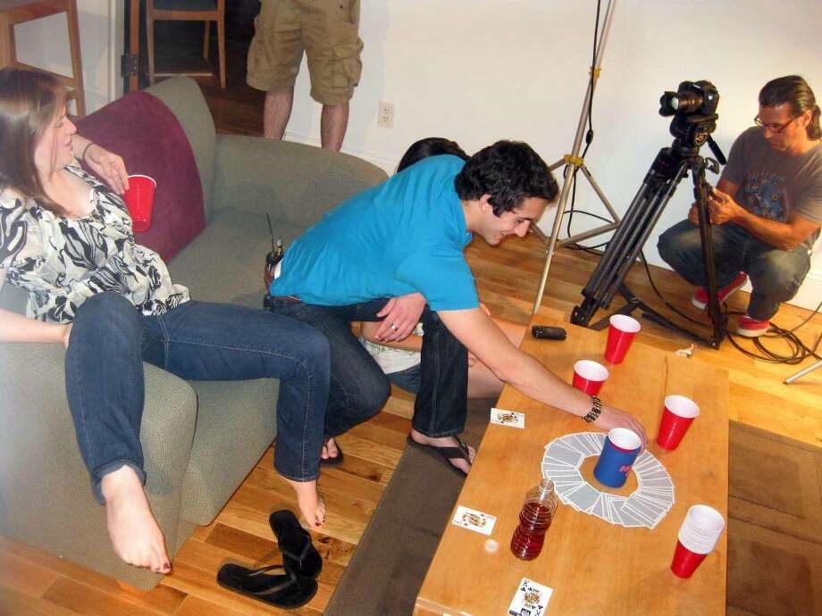 Western Connecticut State University theater majors Crystal Schewe and Mike Crispin pose as college students at a party while a photographer from ACM Productions prepares to record them on Wednesday. The students filmed three video vignettes that illustrate the consequences of drinking alcohol and doing drugs. Photo: Vinti Singh / The News-Times