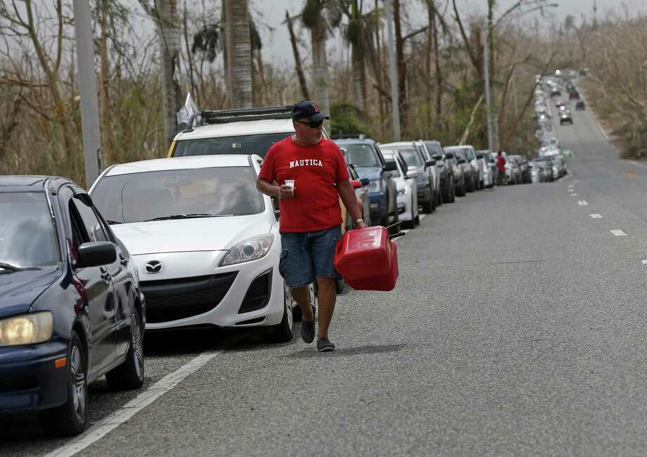 A man with gas cans walks past a long line of cars as people queue up to buy gas in the aftermath of Hurricane Maria, in Morovis, Puerto Rico, Wednesday, Sept. 27, 2017. A week since the passing of Maria many are still waiting for help from anyone from the federal or Puerto Rican government. But the scope of the devastation is so broad, and the relief effort so concentrated in San Juan, that many people from outside the capital say they have received little to no help. (AP Photo/Gerald Herbert) Photo: Gerald Herbert / Associated Press / Copyright 2017 The Associated Press. All rights reserved.