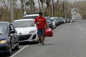 A man with gas cans walks past a long line of cars as people queue up to buy gas in the aftermath of Hurricane Maria, in Morovis, Puerto Rico, Wednesday, Sept. 27, 2017. A week since the passing of Maria many are still waiting for help from anyone from the federal or Puerto Rican government. But the scope of the devastation is so broad, and the relief effort so concentrated in San Juan, that many people from outside the capital say they have received little to no help. (AP Photo/Gerald Herbert)