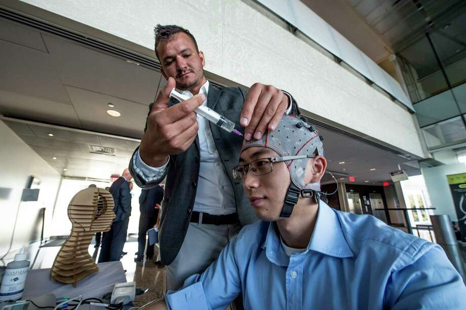 Slav Dimov of g.tec neurotechnology USA adds fluid to the receptors on an EEG cap worn by Fan Cao. The fluid increases conductivity, to better measure electrical activity in the brain. (Skip Dickstein/Times Union) Photo: SKIP DICKSTEIN, Albany Times Union / 40041686A