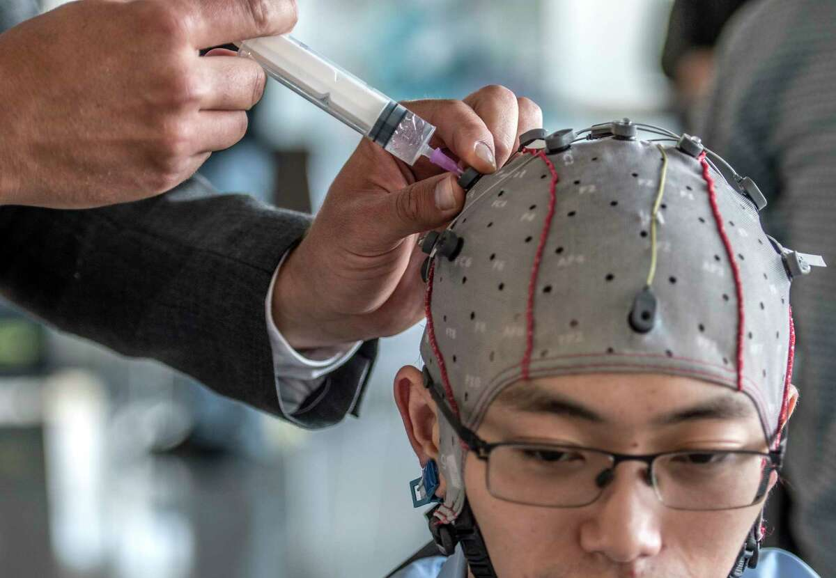 Slav Dimov adds fluid to the receptors on the skull cap worn by Fan Cao of GTec during a demonstration of connectivity to measure brain waves at the opening of Center For Neurotechnology at the University at Albany Sciences Campus Tuesday Oct. 3, 2017 in Rensselaer, N.Y. (Skip Dickstein/Times Union)