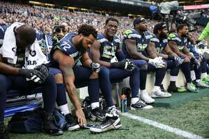 A group of Seahawks sits during the national anthem in protest of police brutality and injustice in the US, before their game against the Indianapolis Colts at CenturyLink Field on Sunday.