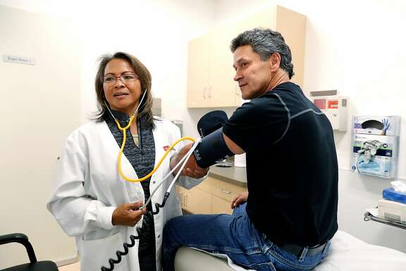 Fred Pons with nurse supervisor Maria Gamulo-Owen on Tues. Oct. 3, 2017, at the Order of Malta Clinic of Christ the Light Church, in Oakland, Ca. Pons received care earlier for his potentially fatal spider bite to his hand at the clinic.