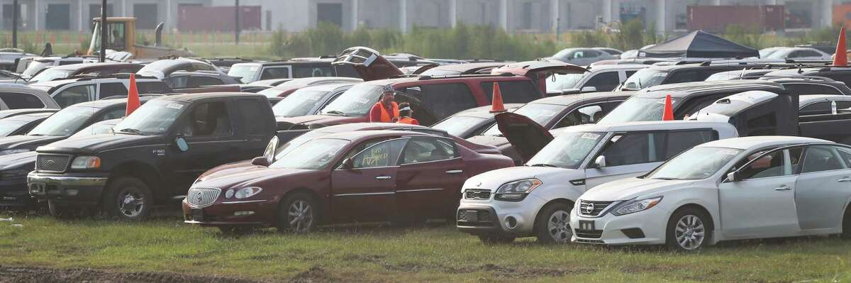 Thousands of flood-damaged cars are at the parking lot of the Royal Purple Raceway in Baytown being examined by adjusters. The lot is being used by Copart USA to store cars until they can be placed for bid.