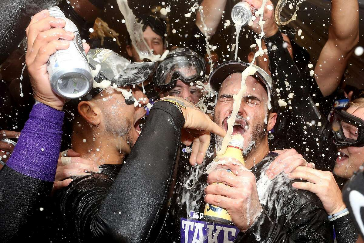 DENVER, CO - SEPTEMBER 30: Carlos Gonzalez #5 and Nolan Arenado #28 of the Colorado Rockies are doused by his teammates in the lockerroom at Coors Field on September 30, 2017 in Denver, Colorado. Although losing 5-3 to the Los Angeles Dodgers, the Rockies celebrated clinching a wild card spot in the post season. (Photo by Matthew Stockman/Getty Images) *** BESTPIX ***