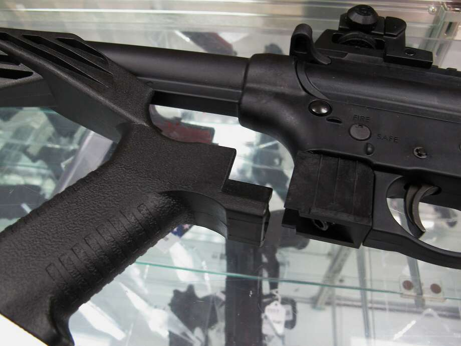 """FILE - This Feb. 1, 2013, file photo shows a """"bump"""" stock next to a disassembled .22-caliber rifle at North Raleigh Guns in Raleigh, N.C. The gunman who unleashed hundreds of rounds of gunfire on a crowd of concertgoers in Las Vegas on Monday, Oct. 2, 2017, attached what is called a """"bump-stock"""" to two of his weapons, in effect converting semiautomatic firearms into fully automatic ones. (AP Photo/Allen Breed, File) Photo: Allen Breed, Associated Press"""