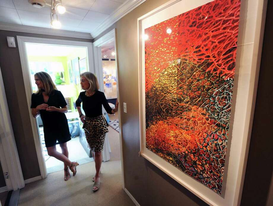 "Camilla Cook, left, and Sandra Morgan stand near a work by artist and photographer Janice Mehlman of Brooklyn, N.Y., titled ""Inappropriate Entanglements,"" that is part of the ""Punch & Sizzle"" art show featuring five artists at the SM Home Art Gallery in Greenwich, Conn., Thursday, Sept. 28, 2017. Morgan is the owner of the gallery and Cook is an associate art director there. The shows runs until November 18, 2017 at the gallery located at 70 Arch Street in Greenwich. Photo: Bob Luckey Jr. / Hearst Connecticut Media / Greenwich Time"