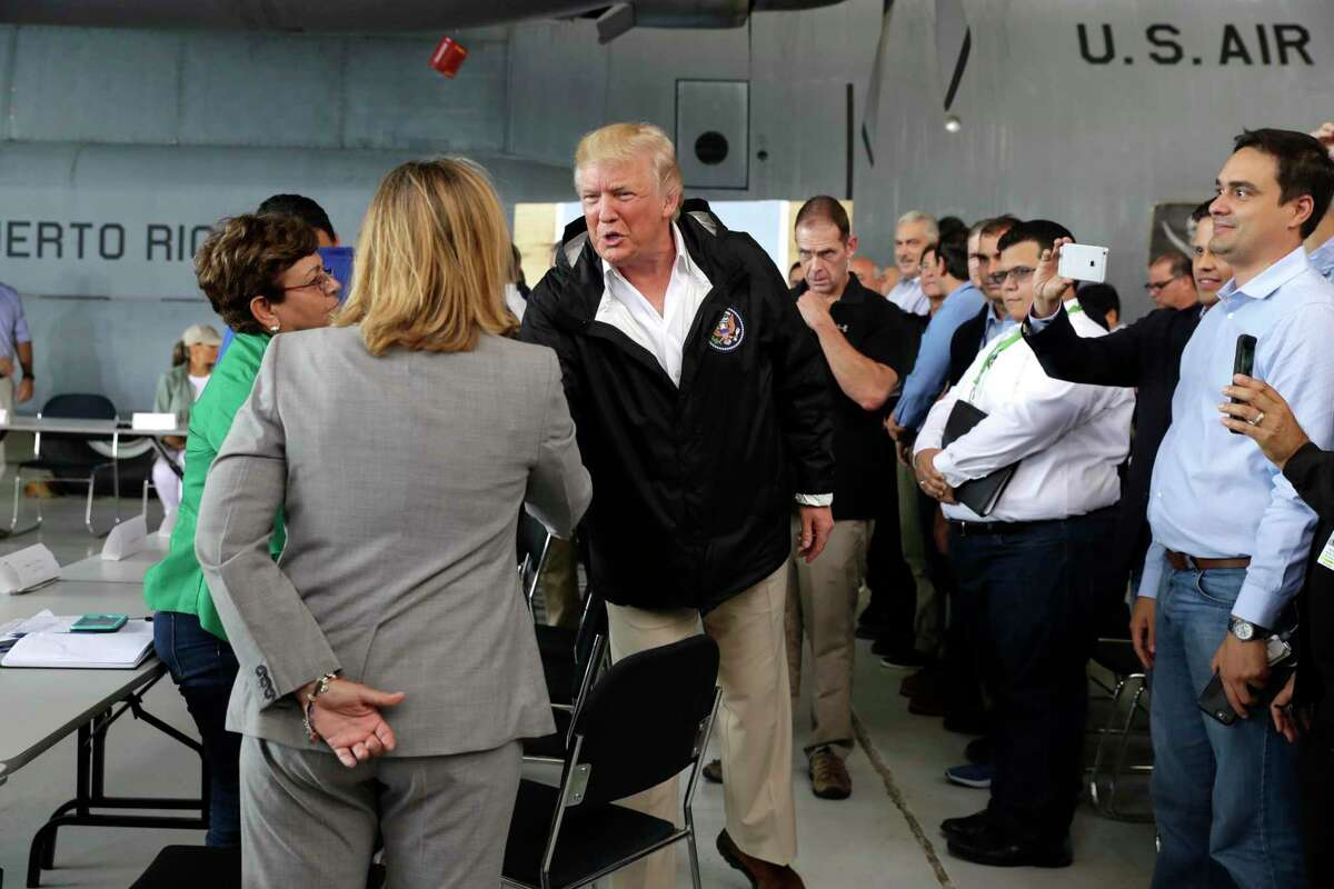 President Donald Trump shakes hands with San Juan Mayor Carmen Yulia Cruz during a meeting after the president's arrival Tuesday in Puerto Rico.