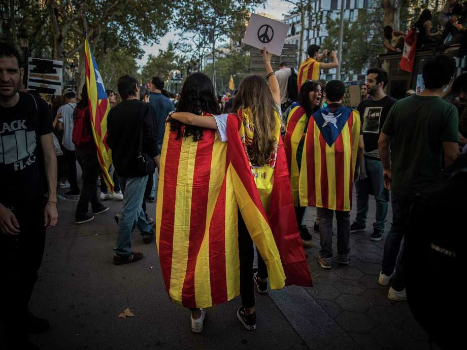 Two girls, one with a Catalan independence flag and the other with a Spanish flag, walk together as demonstrators gather in Barcelona, Spain, Tuesday. Photo: Santi Palacios, STF / Copyright 2017 The Associated Press. All rights reserved.