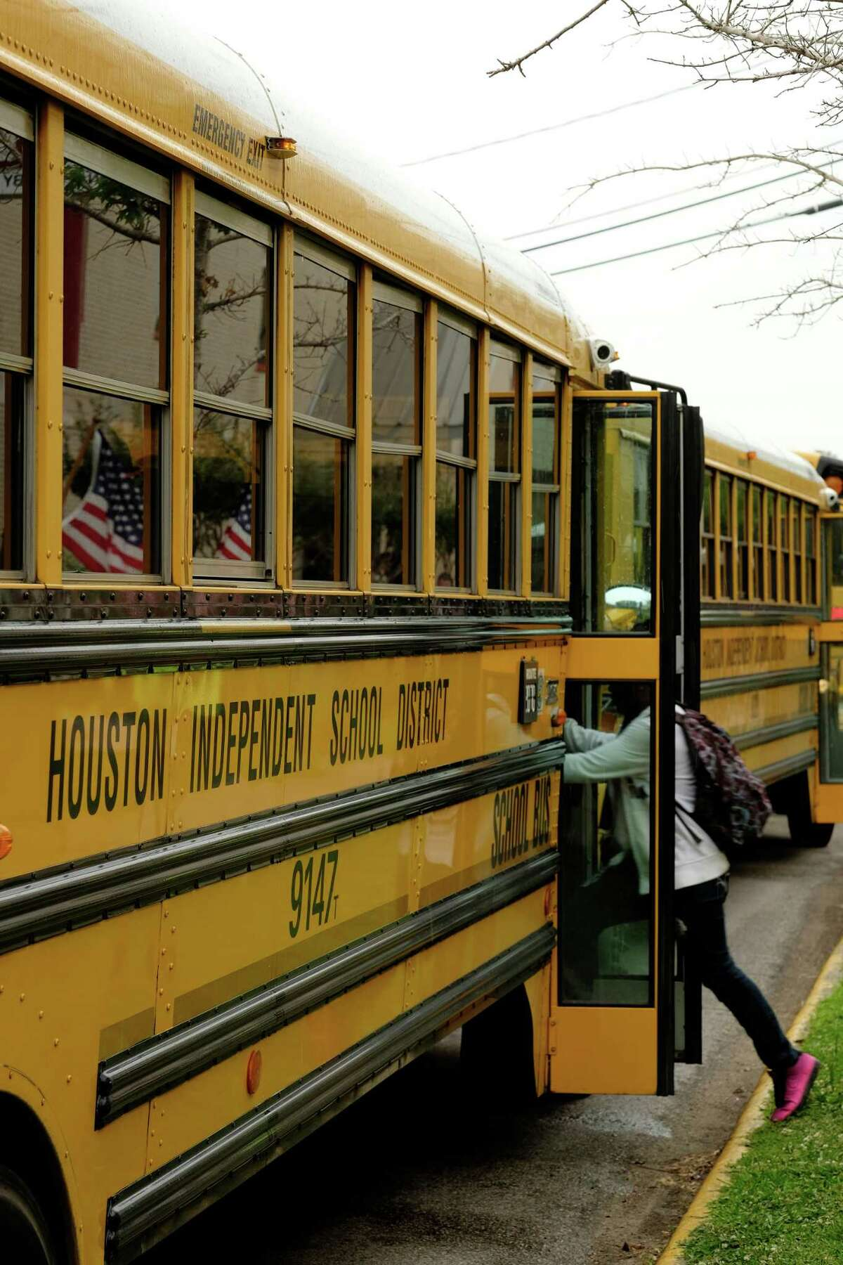 With American flags in the background, Bellaire Senior High School students in Houston make their way to their respective buses after the final bell on May 26, 2014. ( Â TODD SPOTH)