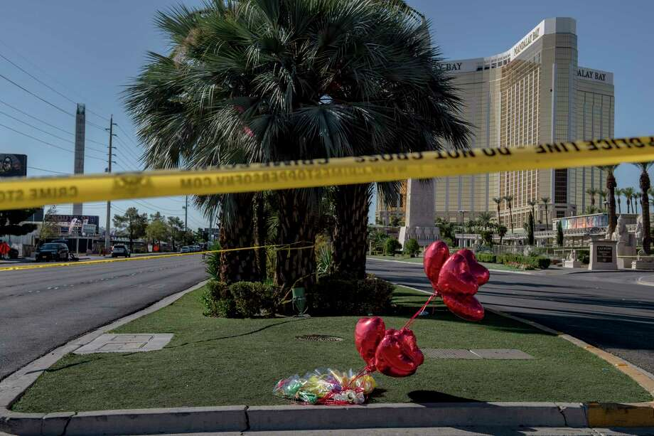 Flowers, balloons and police tape at the intersection of Las Vegas Boulevard and Reno Avenue near the Mandalay Bay Resort and Casino, from where a lone gunman's barrage left at least 59 dead and 527 injured, in Las Vegas. (Hilary Swift/The New York Times) Photo: HILARY SWIFT, STR / NYTNS