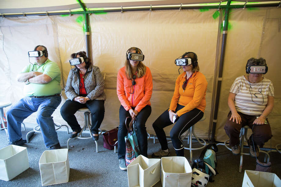"""Visitors take virtual reality tours of refugee camps around the world at Doctors Without Borders' visiting exhibit """"Forced From Home"""" at Denny Park on Oct. 3, 2017. Photo: GRANT HINDSLEY, SEATTLEPI.COM / SEATTLEPI.COM"""