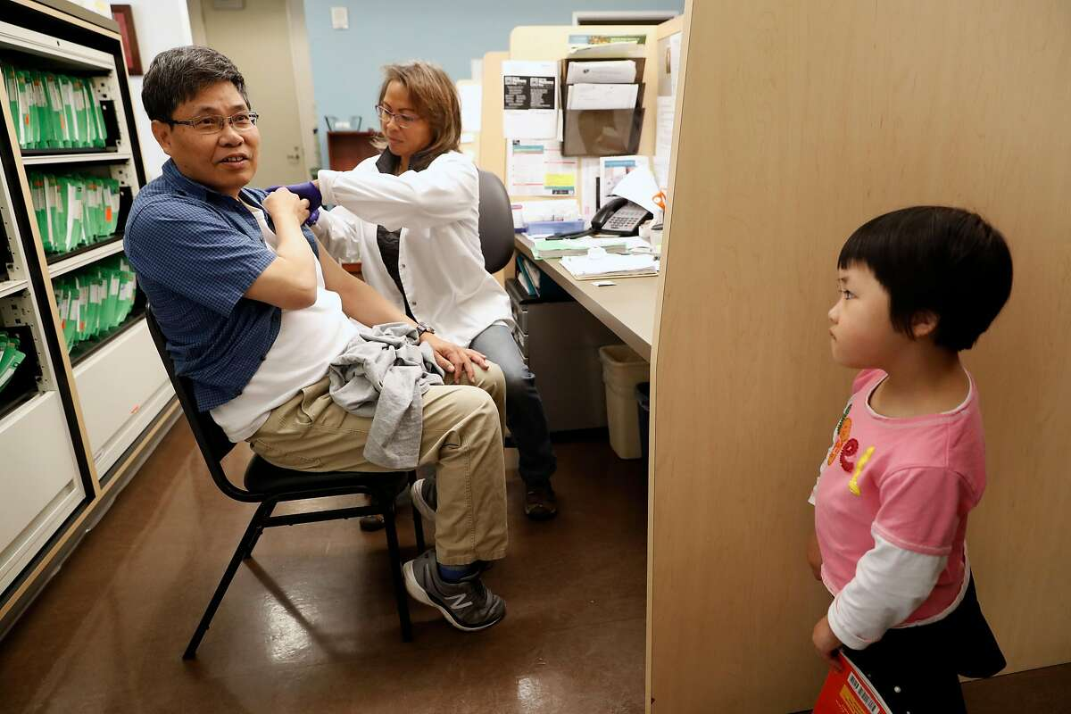 Skylar Chan, 4 wathces her father Johnson Chan get his flu shot shot from nurse supervisor Maria Gamulo-Owen on Tues. Oct. 3, 2017, at the Order of Malta Clinic at the Christ the Light Church, in Oakland, Ca.