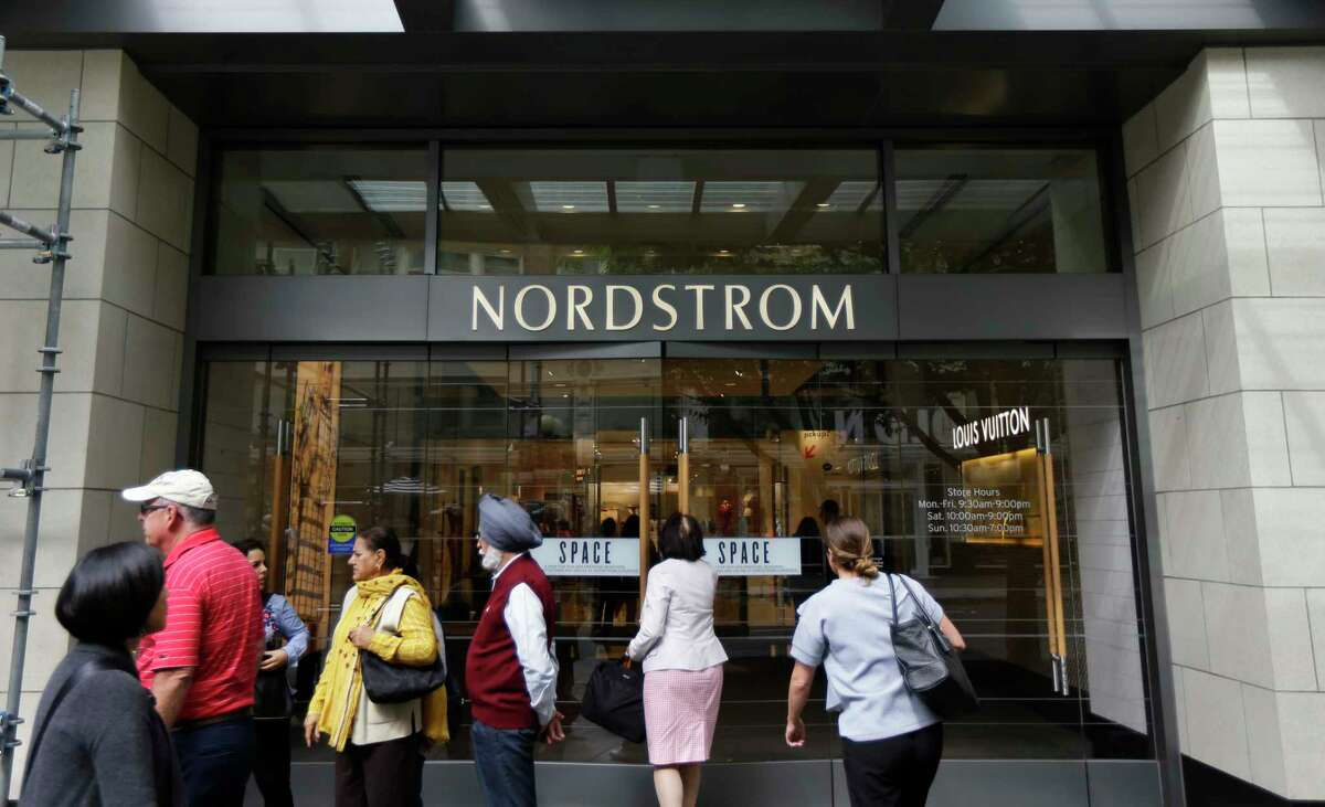In this Wednesday, Sept. 13, 2017, photo, people stand near an entrance for Nordstrom Inc.'s flagship store in downtown Seattle. In information released Tuesday, Oct. 3, 2017, the National Retail Federation is forecasting holiday sales for the November and December period to rise between 3.6 percent and 4 percent to $678.75 billion to $682 billion. (AP Photo/Ted S. Warren) ORG XMIT: WATW202