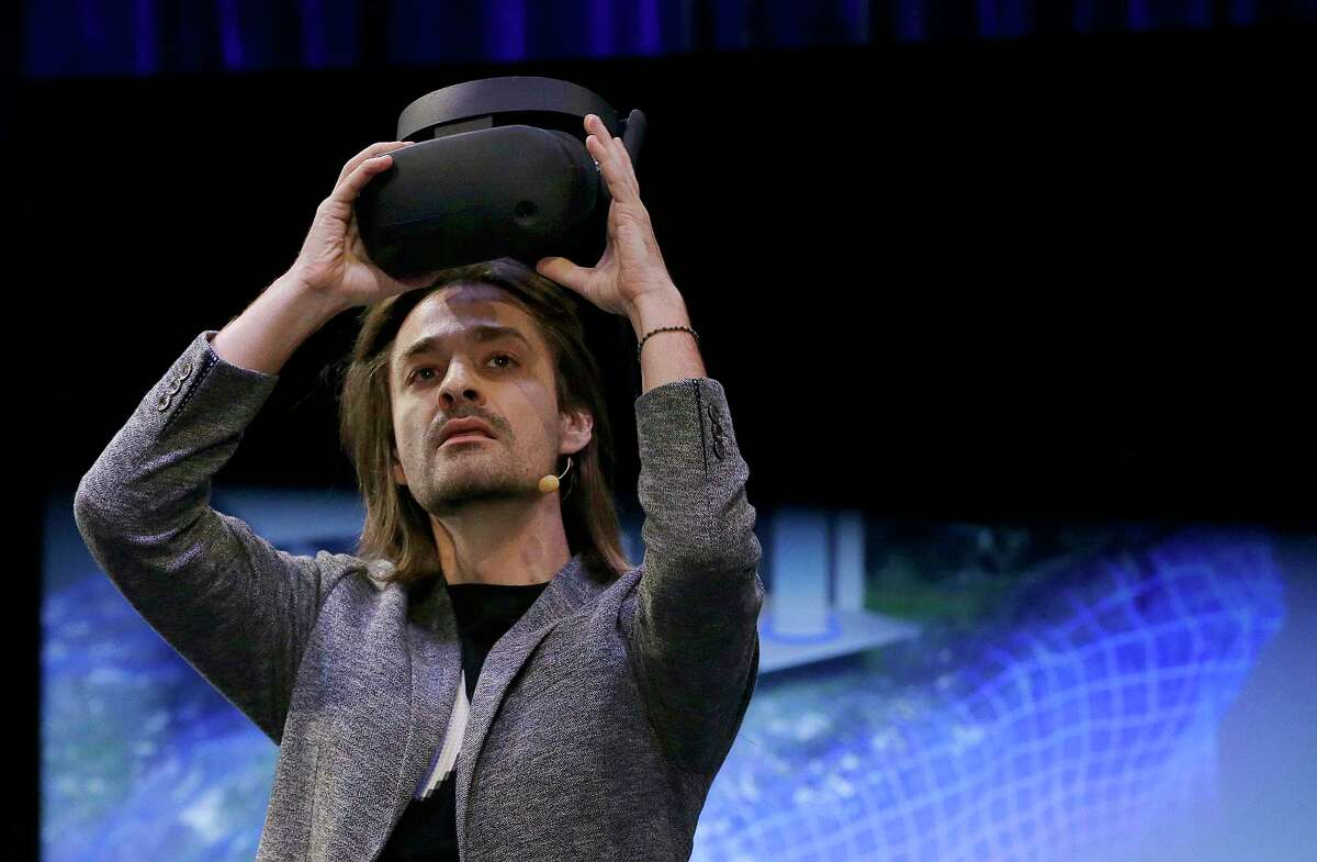 Microsoft Technical Fellow Alex Kipman holds an HMD Odyssey virtual reality headset, Tuesday, Oct. 3, 2017, in San Francisco. Microsoft is touting virtual reality headsets made by other companies in hopes of establishing personal computers running on its Windows 10 operating system as the best way for people to experience artificial worlds. The devices unveiled on Tuesday include a Samsung headset called the HMD Odyssey. The $500 headset requires a connection to a PC running on a Windows 10 update being released Oct. 17. (AP Photo/Ben Margot) ORG XMIT: CABM101