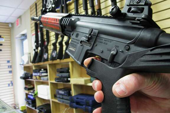"""An employee of a Raleigh, N.C., gun store demonstrates how a """"bump stock"""" works. The mechanism converts semi-automatic firearms into fully automatic ones."""