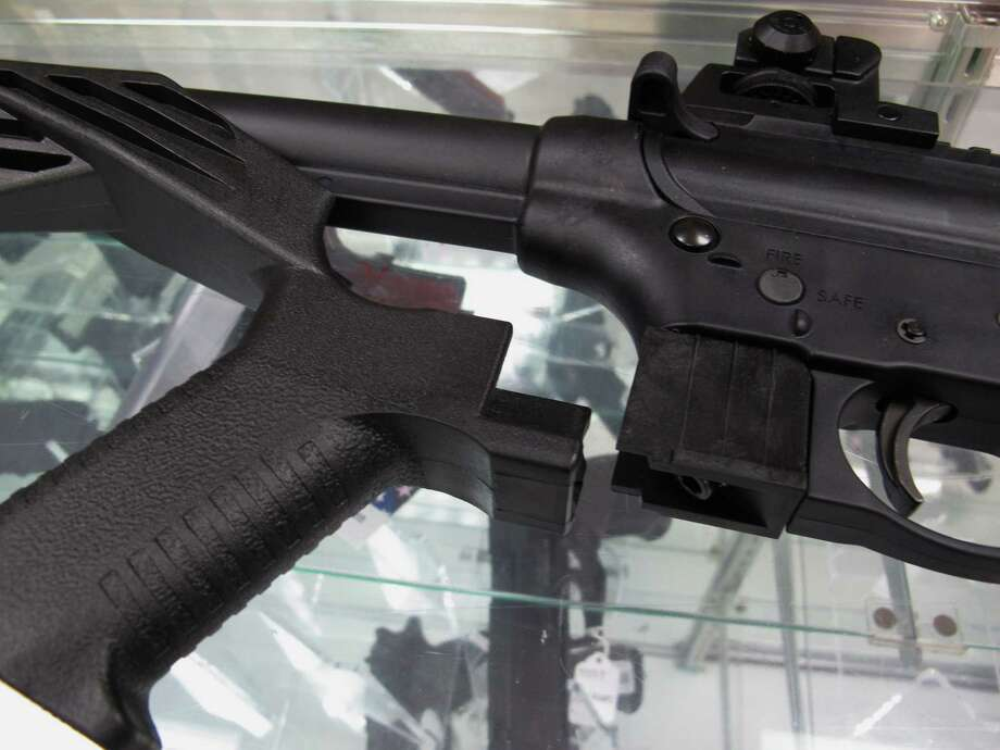 """FILE - This Feb. 1, 2013, file photo shows a """"bump"""" stock next to a disassembled .22-caliber rifle at North Raleigh Guns in Raleigh, N.C. The gunman who unleashed hundreds of rounds of gunfire on a crowd of concertgoers in Las Vegas on Monday, Oct. 2, 2017, attached what is called a """"bump-stock"""" to two of his weapons, in effect converting semiautomatic firearms into fully automatic ones. (AP Photo/Allen Breed, File) Photo: Allen Breed, STF / Copyright 2017 The Associated Press. All rights reserved."""