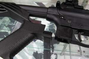 """FILE - This Feb. 1, 2013, file photo shows a """"bump"""" stock next to a disassembled .22-caliber rifle at North Raleigh Guns in Raleigh, N.C. The gunman who unleashed hundreds of rounds of gunfire on a crowd of concertgoers in Las Vegas on Monday, Oct. 2, 2017, attached what is called a """"bump-stock"""" to two of his weapons, in effect converting semiautomatic firearms into fully automatic ones. (AP Photo/Allen Breed, File)"""