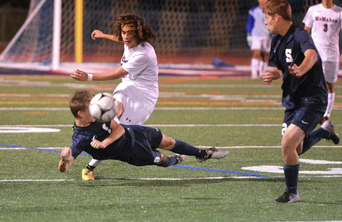 Brien McMahon's # 18 Christopher Ocampo gets the ball over Staples defender #9 Vaughan Sealey during boys soccer action at Brien McMahon High School on Tuesday October 3, 2017 in Norwalk Conn.