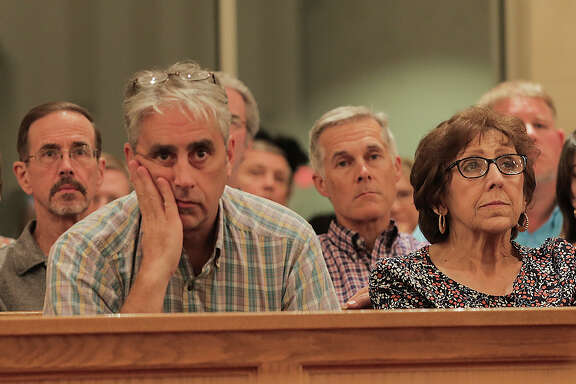 Andrew Moll who owns a home in Bear Creek that was flooded with four feet of water for two weeks listens to a town hall meeting at St. John Vianney Catholic Church for Harvey response on Tuesday, Oct. 3, 2017, in Houston.
