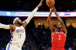Houston Rockets guard Chris Paul (3) shoots as Oklahoma City Thunder forward Carmelo Anthony (7) defends during the first quarter of an NBA preseason basketball game in Tulsa, Okla., Tuesday, Oct. 3, 2017. (AP Photo/Sue Ogrocki)