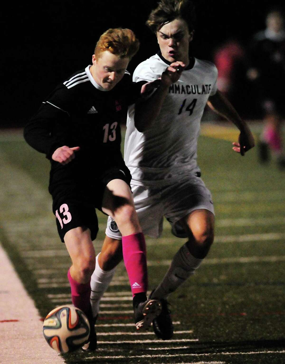 Masuk's Matthew Machan, left, heads off Immaculate's Quinn Guth during boys soccer action in Monroe, Conn., on Tuesday Oct. 3, 2017.