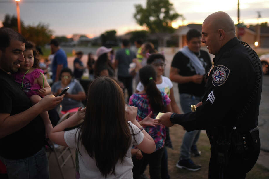 Sgt. Jimmy Young with the Midland Police Department gives out police badge stickers during a National Night Out party at La Roca The Rock church on Oct. 3, 2017. James Durbin/Reporter-Telegram Photo: James Durbin