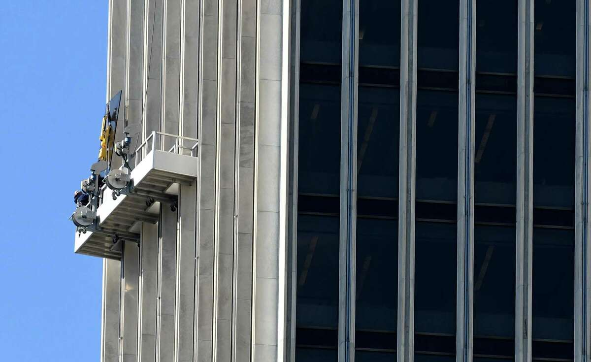 Workers replace a window on Corning Tower at Empire State Plaza on Tuesday, Oct. 3, 2017, in Albany, N.Y. (Will Waldron/Times Union)