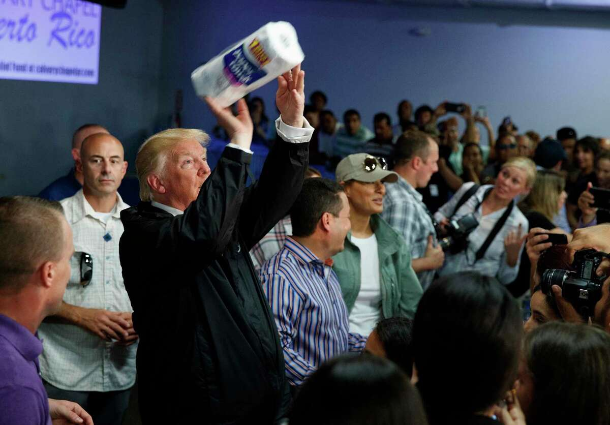 President Donald Trump tosses paper towels into a crowd as he hands out supplies at Calvary Chapel, Tuesday, Oct. 3, 2017, in Guaynabo, Puerto Rico. Trump is in Puerto Rico to survey hurricane damage. (AP Photo/Evan Vucci) ORG XMIT: PREV128