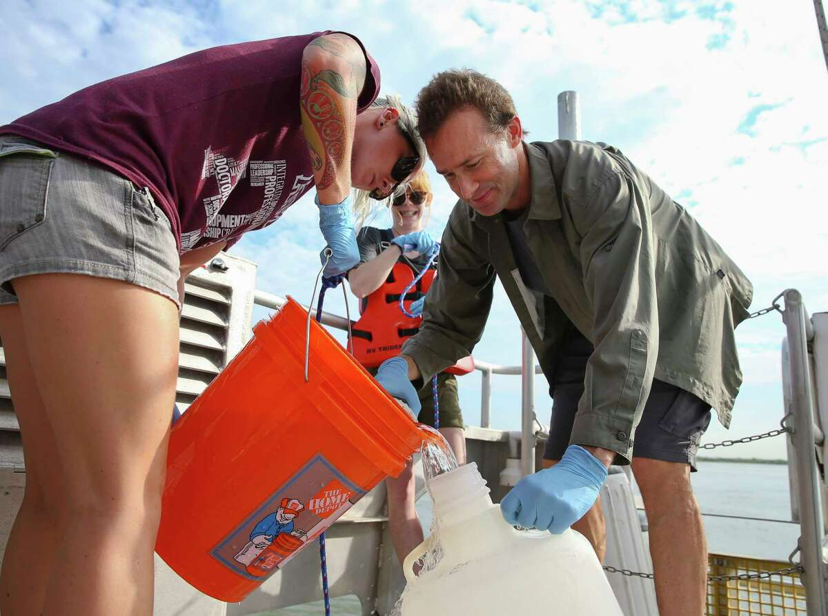 Karl Kaiser and students Amanda Fay, left, and Laura Leonard collect water along the Ship Channel.