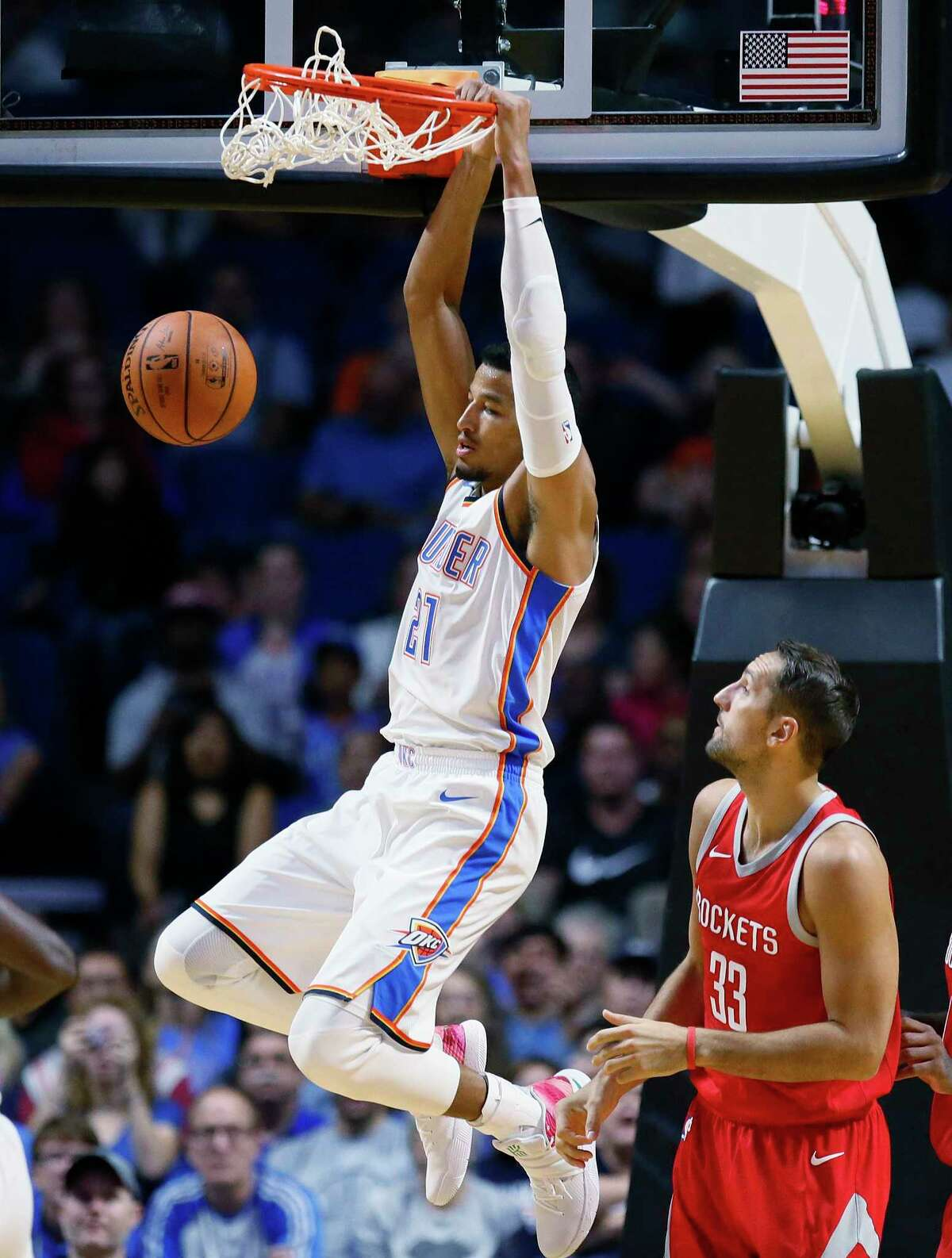 Oklahoma City Thunder guard Andre Roberson (21) hangs from the basket in front of Houston Rockets forward Ryan Anderson (33) during the first quarter of an NBA preseason basketball game in Tulsa, Okla., Tuesday, Oct. 3, 2017. (AP Photo/Sue Ogrocki)