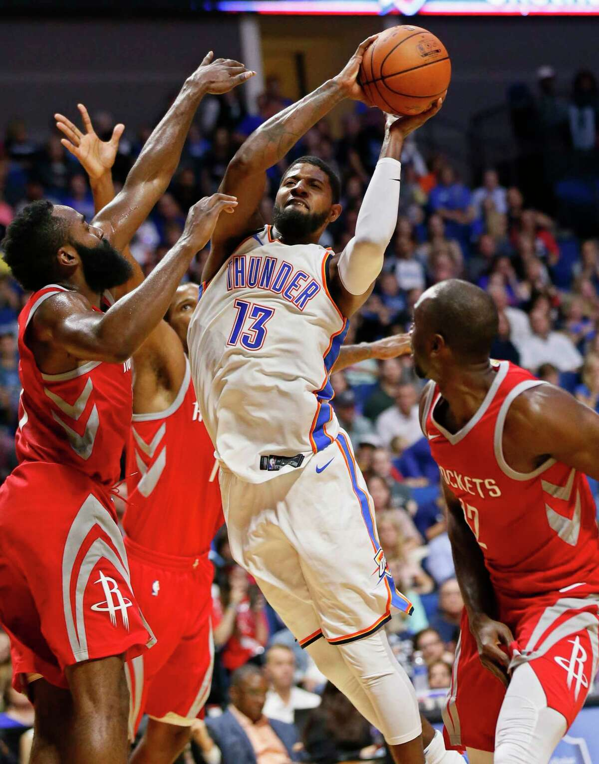 New Thunder forward Paul George, right, leans away from the Rockets' James Harden, left, and Trevor Ariza to try a shot. George finished with 15 points.