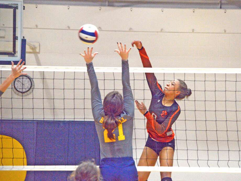 Edwardsville freshman Alexa Harris, right, goes up for a kill during the first game of Tuesday's Southwestern Conference match at O'Fallon.