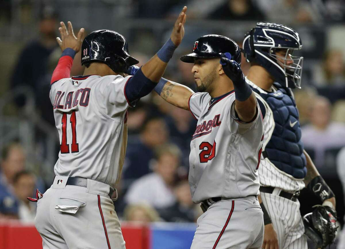 Minnesota Twins' Jorge Polanco (11) and Eddie Rosario (20) celebrate after Polanco scored on Rosario's first-inning, two-run home run in the American League wild-card playoff baseball game in New York, Tuesday, Oct. 3, 2017. New York Yankees catcher Gary Sanchez is at right. (AP Photo/Kathy Willens)