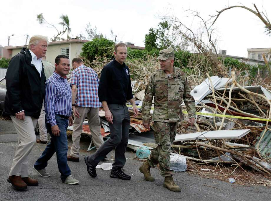 President Donald Trump walks with FEMA administrator Brock Long, second from right, and Lt. Gen. Jeff Buchanan, right as he tours an area affected by Hurricane Maria in Guaynabo, Puerto Rico, Tuesday, Oct. 3, 2017. Trump is visiting Puerto Rico in the wake of Hurricane Maria. Photo: Evan Vucci, AP / AP