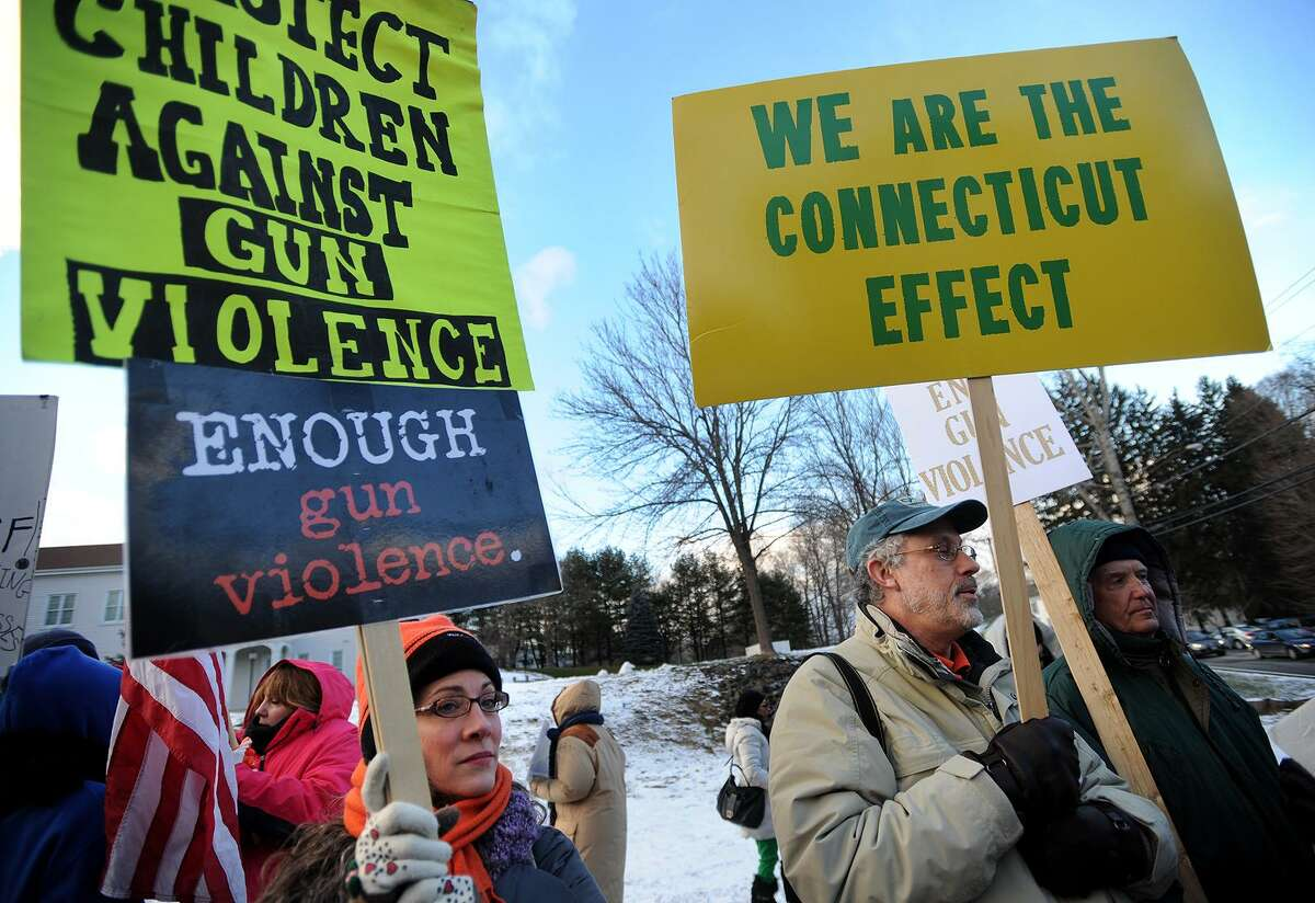 Shina Tarantino, left, of Stamford, and Jonathan Perloe, of Greenwich, participate in a gun control rally outside the National Shooting Sports Foundation's corporate headquarters at 11 Mile Hill Road in Newtown, Conn. on Monday, January 18, 2016.