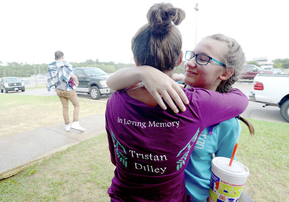 Larkin Bryant (left) hugs Keeleigh Abshire as students and other members of the community gather following a vigil in honor of Tristan Dilley at Silsbee High School Tuesday. The vigil and balloon release was held earlier than scheduled due to the threat of storms.  Friends continued to console one another and share stories of their friend and classmate during a gathering at Taco Bell, Tristan's favorite. Photo taken Tuesday, October 3, 2017 Kim Brent/The Enterprise Photo: Kim Brent / BEN